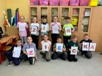Uczniowie_z_klasy_3_z_Wonieścia_trzymają_kartki_z_literami_tworzącymi_napis_DZIEŃ_DZIECKA